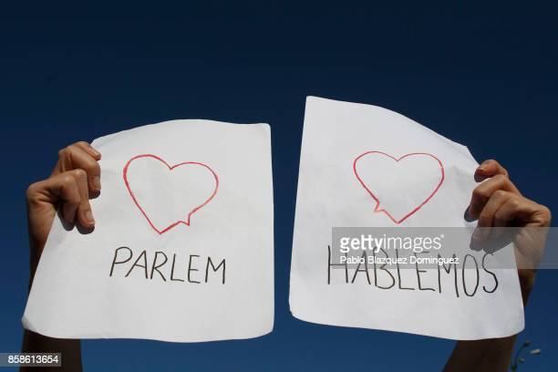 A demonstrator holds a placard reading 'Parlem' and 'Hablemos' during a protest in front of Madrid City Hall under the slogan 'Hablemos' in Spanish...