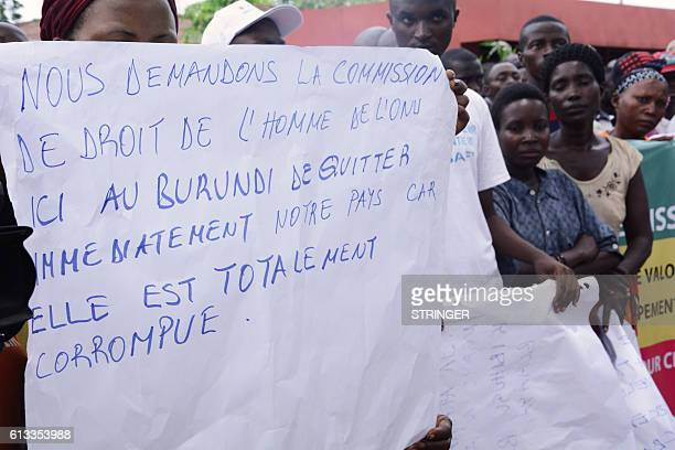 A demonstrator holds a placard reading Since it is totally corrupted we request the United Nations Commission on Human Rights here in Burundi to...