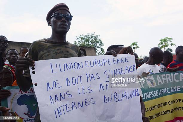A demonstrator holds a placard reading The European Union must not interfere in Burundian home affairs as people protest against the European Union...