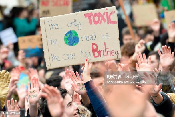 A demonstrator holds a placard reading 'The only toxic the Earth need is the one by Britney ' during a demonstration against climate change on March...