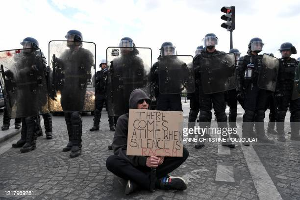 Demonstrator holds a placard reading 'there comes a time when silence is racism' in front of French Gendarmes on the place de la Concorde, in Paris...