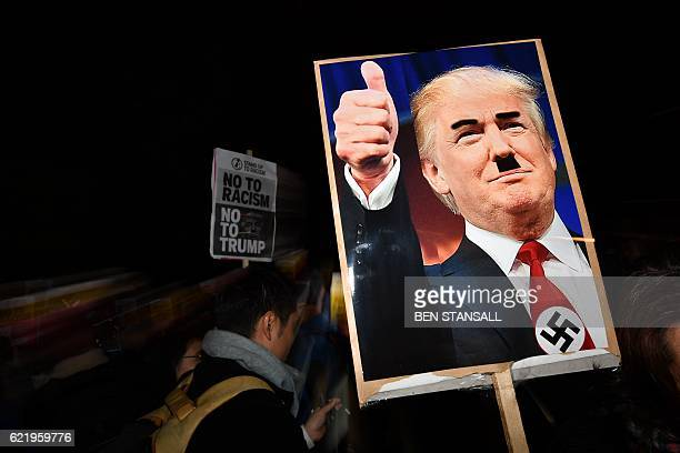 TOPSHOT A demonstrator holds a placard showing a picture of US Presidentelect Donald Trump modified to add a swastika and an Adolf Hitlerstyle...