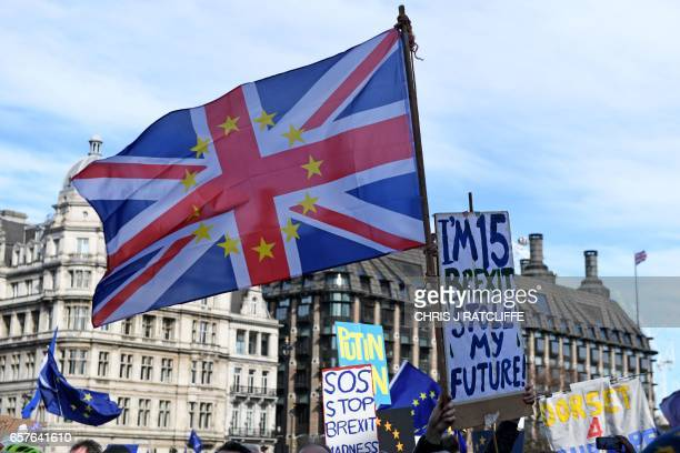 """Demonstrator holds a placard that reads """"I'm 15 and Brexit stole my Future"""" alongside a Union flag during an anti Brexit, pro-European Union march in..."""