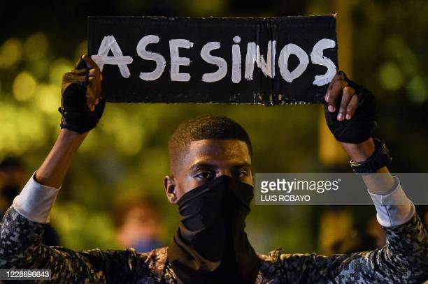 """Demonstrator holds a placard that reads """"Murderers"""" during a protest outside the army's third brigade headquarters in Cali, Colombia on September 24,..."""