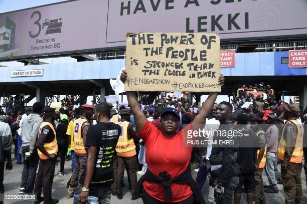 Demonstrator holds a placard to protest against abuses by the Special Anti-Robbery Squad at the Lekki toll Plaza in Lagos, on October 12, 2020. -...