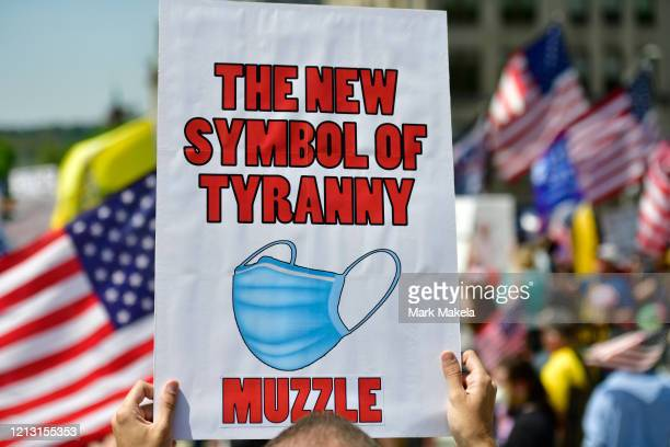 A demonstrator holds a placard with a face mask stating THE NEW SYMBOL OF TYRANNY MUZZLE rallying outside the Pennsylvania Capitol Building to...