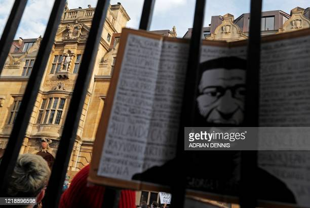Demonstrator holds a placard with an image depicting George Floyd, during a protest calling for the removal of a statue of British businessman and...
