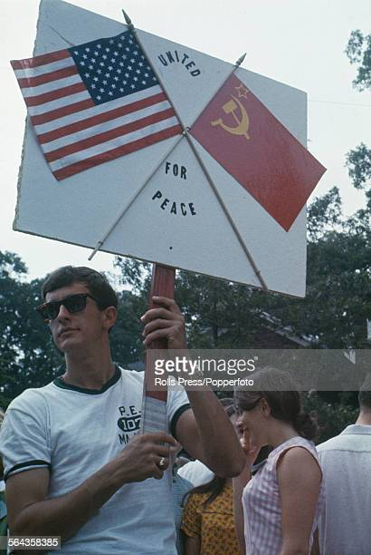 A demonstrator holds a placard with the US and Soviet flags and the slogan 'United for Peace' outside the Glassboro Summit Conference in New Jersey...