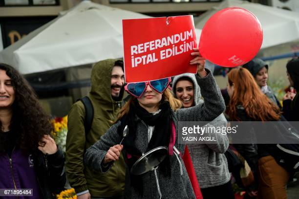 """Demonstrator holds a placards reading """"Referendum should be cancelled"""" during a protest at the Kadikoy district in Istanbul on April 23, 2017..."""