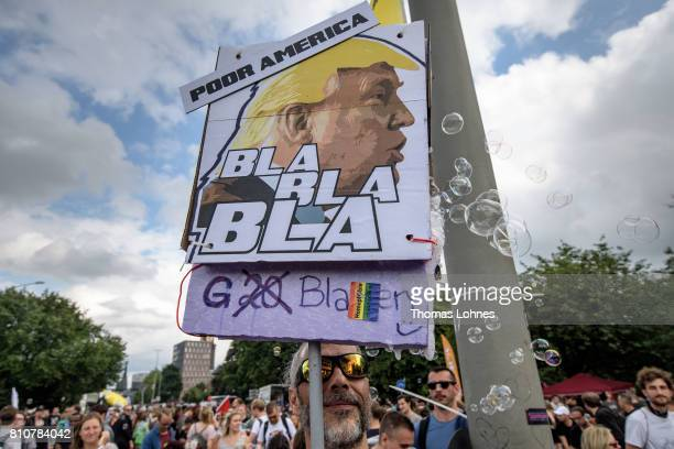 A demonstrator holds a plakat with the face of the US President Donald Trump and the slogan 'Bla Bla Bal G20 Bubbels' while he attend a protesters...