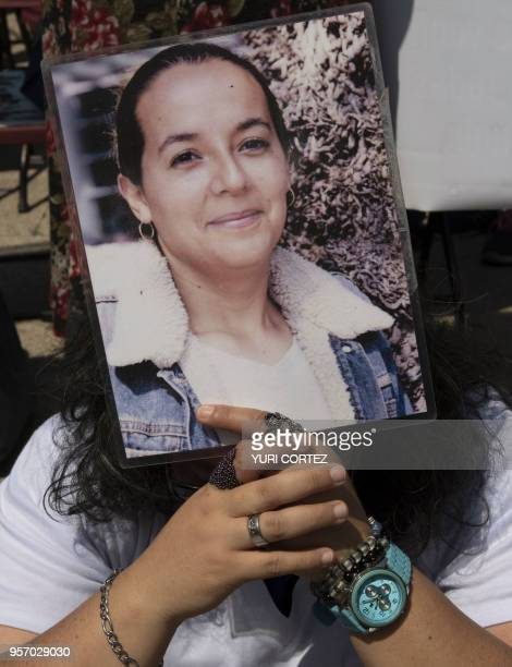 A demonstrator holds a portrait of a missing relative during a march to demand the Mexican government answers about their loved ones whereabouts as...