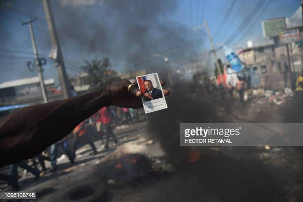 TOPSHOT A demonstrator holds a portrait of former Haitian president JeanBertrand Aristide during a march through the streets of PortauPrince on...