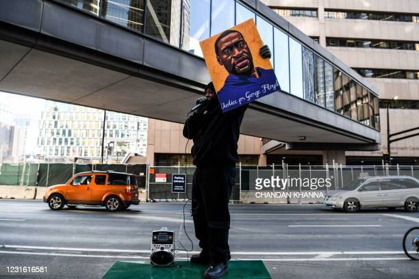 Demonstrator holds a portrait of George Floyd outside the Hennepin County Government Center on March 9, 2021 in Minneapolis, Minnesota. - Jury...