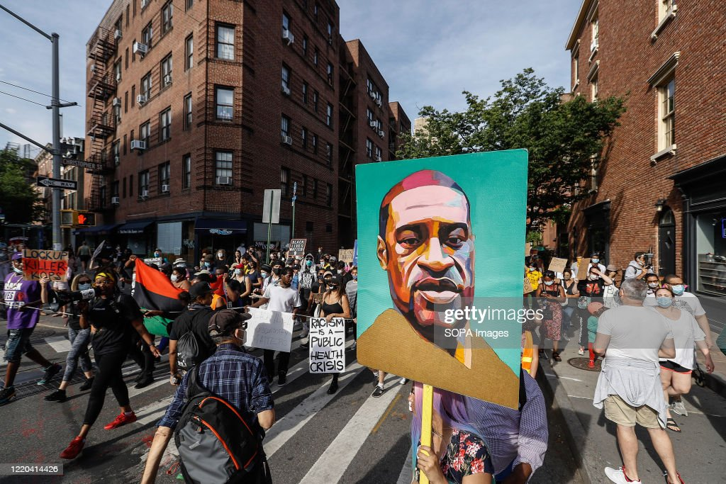 A demonstrator holds a portrait of George Floyd while... : News Photo