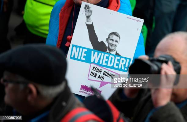 "Demonstrator holds a poster depicting Bjoern Hoecke, AfD leader in Thuringia, raising his arm and captioned ""Never Again"" during a rally themed ""Not..."
