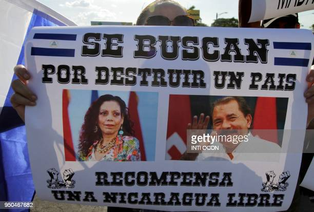 A demonstrator holds a poster depicting Nicaraguan President Daniel Ortega and his wife VicePresident Rosario Murillo reading Wanted for destroying a...