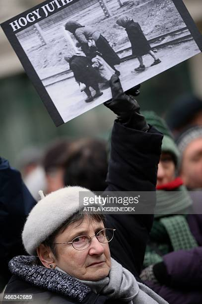 A demonstrator holds a poster of a woman with two children at a Nazi death camp with a text reading 'How were you able to go so far' during an...