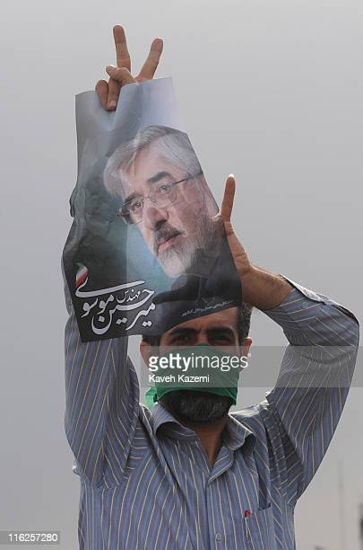 A demonstrator holds a poster of Mir Hossein Mousavi the defeated presidential candidate in Azadi Square Tehran 15th June 2009 He is wearing a green...