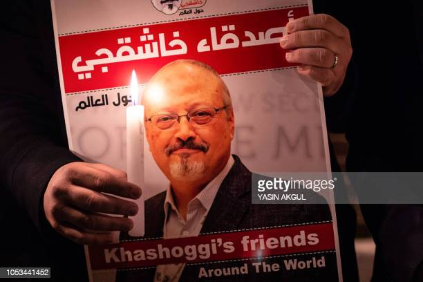 TOPSHOT A demonstrator holds a poster picturing Saudi journalist Jamal Khashoggi and a lightened candle during a gathering outside the Saudi Arabia...