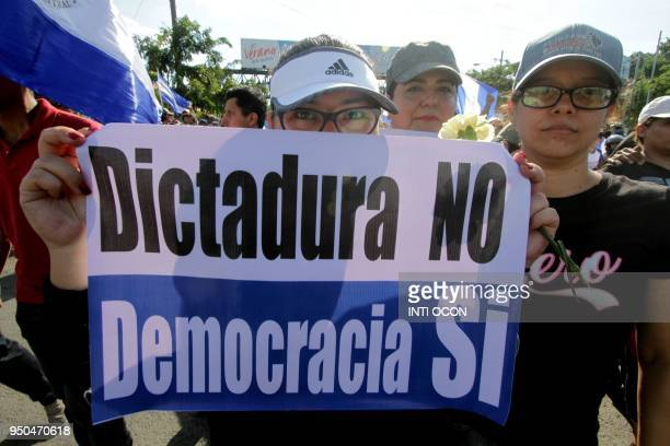 A demonstrator holds a poster reading 'Dictatorship No Democracy Yes' during the 'Walk for Peace and Dialogue' where many demand Nicaraguan President...