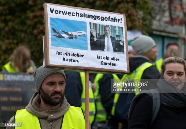 """Demonstrator holds a poster reading the word play """"Danger of Confusion! It's a great box - It's an old Carsten """" during a protest of Germany's UFO..."""