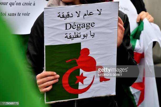 A demonstrator holds a poster representing a silhouette of Algeria's president Abdelaziz Bouteflika on a wheelchair reading oust on the Place de la...