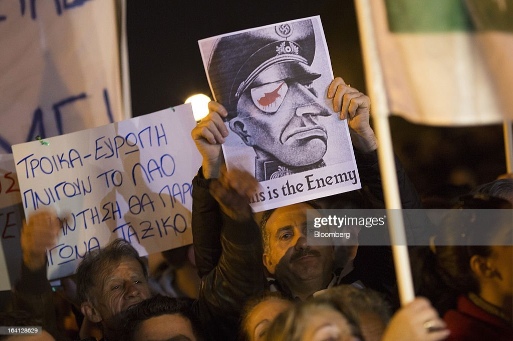 A demonstrator holds a poster showing a caricature Nazi officer with a headline reading 'This is the enemy' during a protest outside the parliament against bank deposit tax plans in Nicosia, Cyprus, on Tuesday, March 19, 2013. Euro-area finance ministers told Cyprus to raise 5.8 billion euros ($7.5 billion) from bank depositors to unlock emergency loans, maintaining the revenue target while suggesting sparing small-scale savers. Photographer: Simon Dawson/Bloomberg via Getty Images