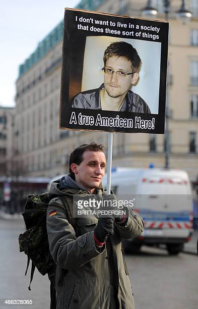A demonstrator holds a poster with the portrait of US whistleblower Edward Snowden as he protests against data preservation in front of the US...
