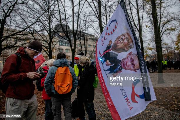 """Demonstrator holds a QAnon flag during protests against modifications to a law called the """"infection protection law"""" prior to a vote on the law in..."""