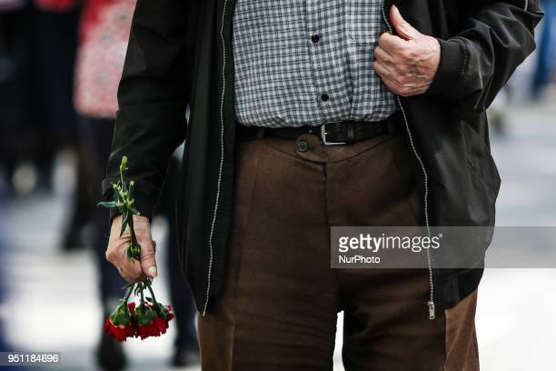 A demonstrator holds a red carnation as he marches through downtown Lisbon on April 25 2018 during a rally to celebrate the 44th anniversary of the...