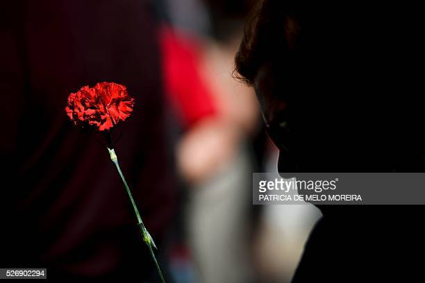 TOPSHOT A demonstrator holds a red carnation symbol of the Portuguese revolution of 1974 during the traditional May Day rally in Lisbon on May 1 2016...