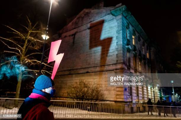 Demonstrator holds a red lightning bolt, the symbol of the Polish women's strike movement, as he takes part in a pro-choice demonstration in front of...