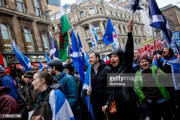 A demonstrator holds a Scottish and Welsh national flags while marching during an All Under One Banner march for Scottish independence in Glasgow...