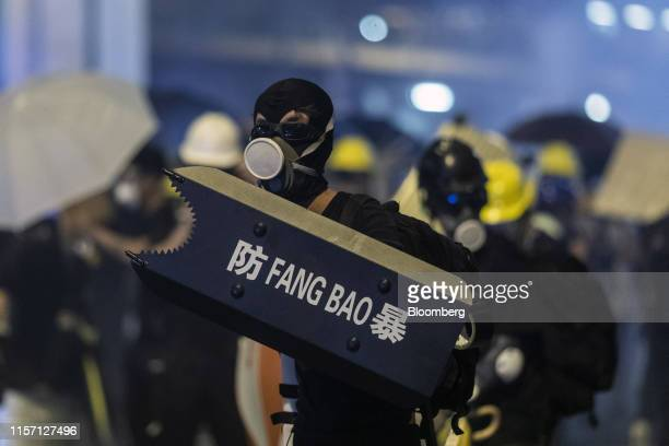 A demonstrator holds a shield reading AntiRiot in Chinese as he stands off against riot police during a protest in the Sheung Wan district of Hong...