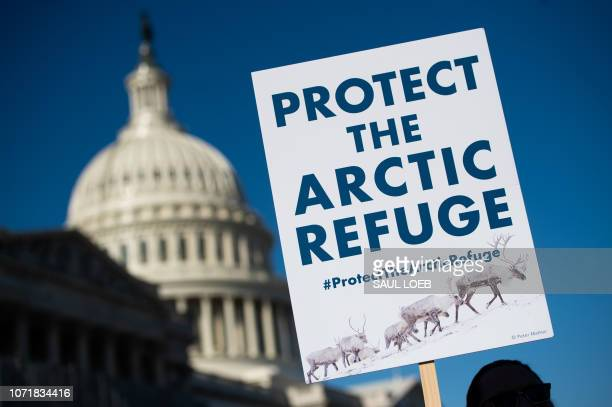 A demonstrator holds a sign against drilling in the Arctic Refuge on the 58th anniversary of the Arctic National Wildlife Refuge during a press...