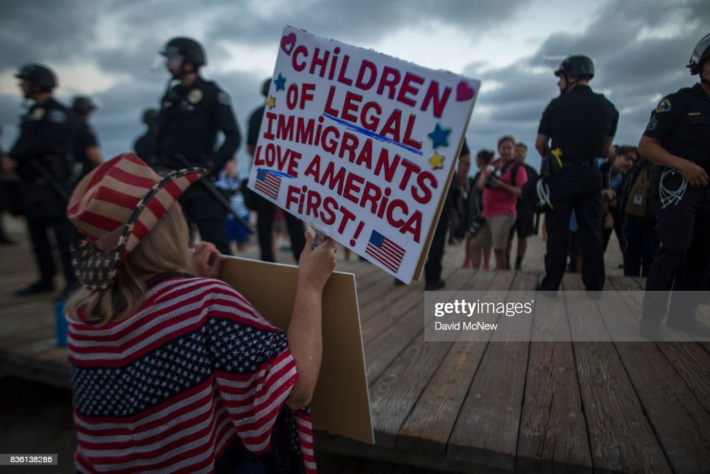 A demonstrator holds a sign as police form a line on the boardwalk to keep demonstrators and counter demonstrators apart during an 'America First' demonstration on August 20, 2017 in Laguna Beach, California. Organizers of the rally describe it as a vigil for victims of illegal immigrants and refugees. Opponents say the demonstration is steeped in racism.