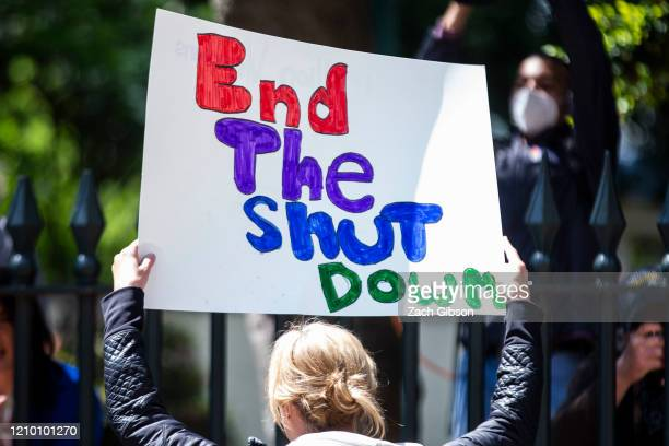 A demonstrator holds a sign at the Virginia State Capitol on April 16 2020 in Richmond Virginia ReOpen Virginia End The Lockdown VA and Virginians...