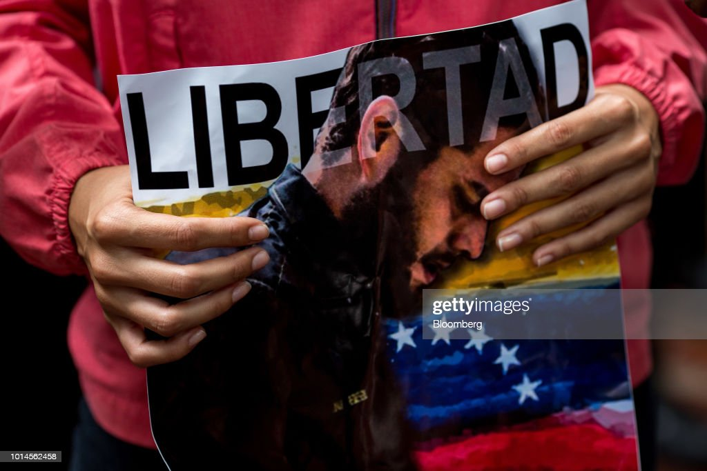 A demonstrator holds a sign displaying the image of detained congressman Juan Requesens during a protest in front of the Organization of American States (OAS) headquarters in Caracas, Venezuela, on Friday, Aug. 10, 2018. Venezuelan President Nicolas Maduro launched a roundup of opponents in tandem with a security sweep in the wake of Saturday's explosive drone attack. Requesens was arrested by intelligence police Tuesday evening and taken from his his east Caracas apartment, security camera footage showed. Photographer: Manaure Quintero/Bloomberg via Getty Images