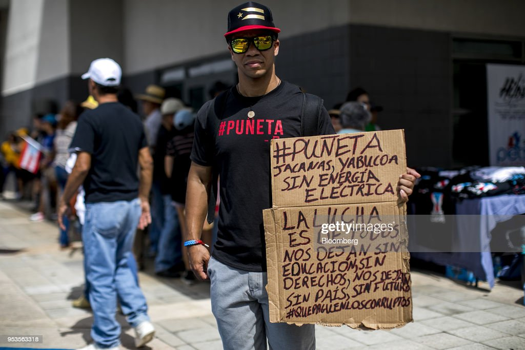 A demonstrator holds a sign during a protest against austerity measures in the Hato Rey neighborhood of San Juan, Puerto Rico, on Tuesday, May 1, 2018. Puerto Rico demonstrators battled police on San Juan's streets as they marched against proposed cuts to retirement benefits and looser labor laws as the bankrupt island seeks to reduce $74 billion of debt. Photographer: Xavier Garcia/Bloomberg via Getty Images