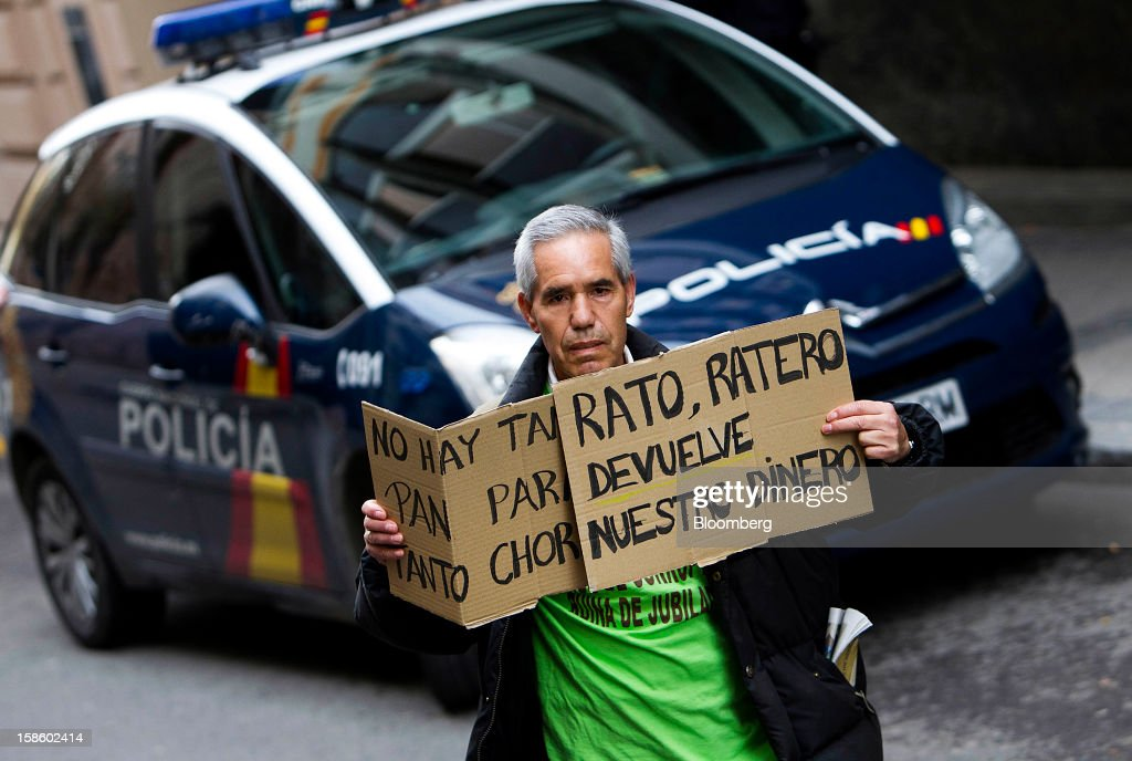A demonstrator holds a sign during a protest against Rodrigo Rato, former managing director of the International Monetary Fund and ex-chairman of Bankia Group, as he testifies at Spain's national court in Madrid, Spain, on Thursday, Dec. 20, 2012. Rato who led the seven-way savings bank merger in 2010 that formed Bankia, has appeared before lawmakers probing how the lender that was nationalized after seeking 23.5 billion euros ($28.5 billion) of state aid helped trigger a new stage of Europe's debt crisis. Photographer: Angel Navarrete/Bloomberg via Getty Images
