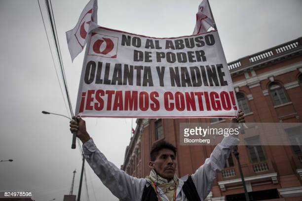 A demonstrator holds a sign during a protest against the detention of former Peruvian President Ollanta Humala and his wife Nadine Heredia outside...