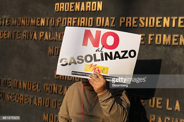 A demonstrator holds a sign during a protest against the gasoline price hike in Mexico City Mexico on Monday Jan 9 2017 The government is letting gas...