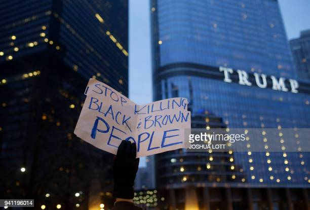 TOPSHOT A demonstrator holds a sign during a protest near Trump International Hotel and Tower on April 2 2018 in Chicago Illinois in response to the...