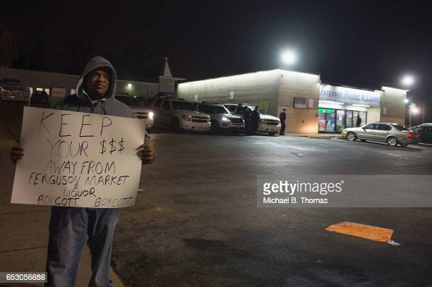 A demonstrator holds a sign during a protests outside the Ferguson Market and Liquor on March 13 2017 in Ferguson Missouri Tension and protest in...