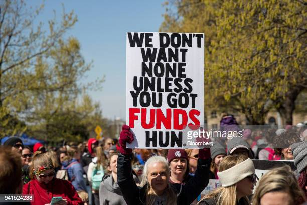 A demonstrator holds a sign during a strike outside the Oklahoma State Capitol building in Oklahoma City Oklahoma US on Tuesday April 3 2018 Hundreds...
