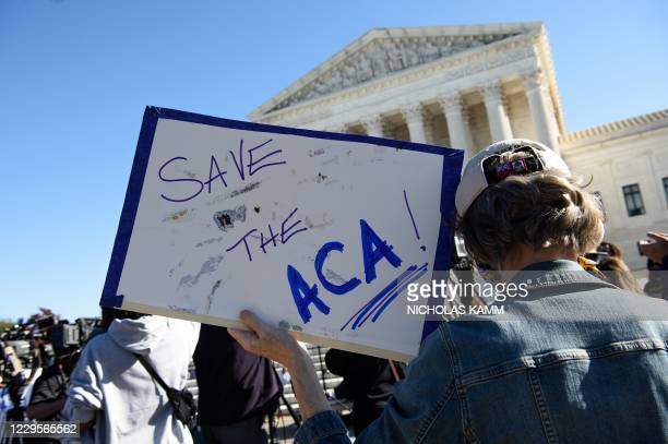 Demonstrator holds a sign in front of the US Supreme Court in Washington, DC, on November 10 as the high court opened arguments in the long-brewing...
