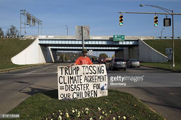 A demonstrator holds a sign in protest of Donald Trump's 2016 Republican presidential nominee position on climate change ahead of early voting in...