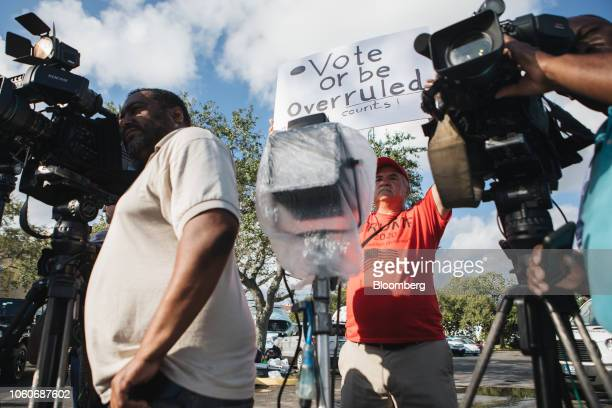 A demonstrator holds a sign near members of the media during a press conference outside the Broward County Supervisor of Elections office in...