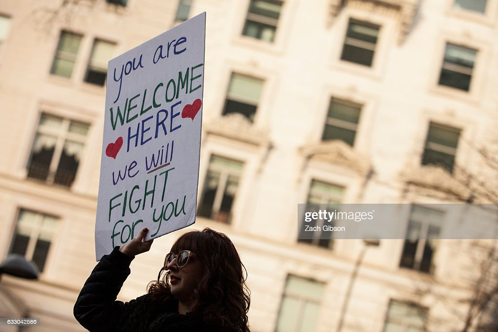 A demonstrator holds a sign outside of the Trump Hotel International during a protest on January 29, 2017 in Washington, DC. Protestors in Washington and around the country gathered to protest President Donald Trump's executive order barring the citizens of Muslim-majority countries Iraq, Syria, Iran, Sudan, Libya, Somalia and Yemen from traveling to the United States.