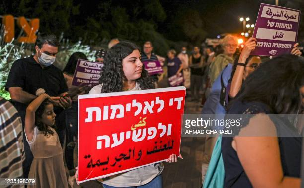 """Demonstrator holds a sign reading Arabic and Hebrew """"enough violence and crime"""" during a protest by Arab Israelis and activists against the..."""
